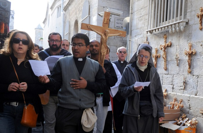 Christians carry a cross on the Via Dolorosa on Good Friday in Jerusalem's Old City