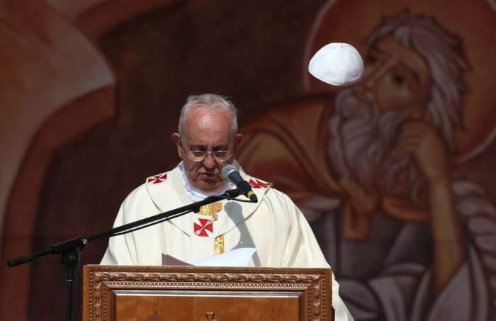 A gust of wind blows off Pope Francis' cap as he speaks during a mass at Amman International Stadium