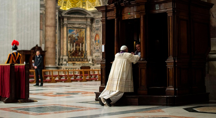 Clergyman hears confession from Pope Francis during penitential liturgy in St. Peter's Basilica at Vatican
