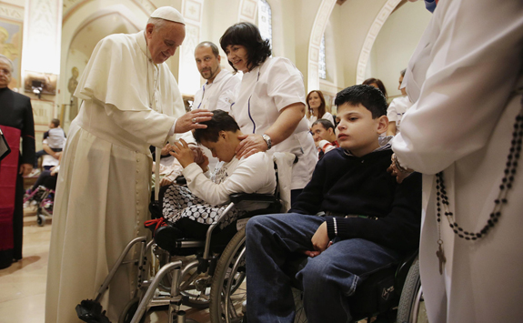 Pope Francis blesses disabled person during visit at Serafico Institute in Assisi