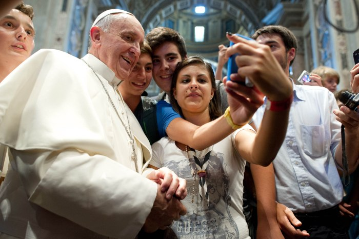 FILE - In this Aug. 28, 2013 file photo provided Thursday, Aug. 29, 2013 by the Vatican newspaper L'Osservatore Romano, Pope Francis has his picture taken inside St. Peter's Basilica with youths from the Italian Diocese of Piacenza and Bobbio who came to Rome for a pilgrimage, at the Vatican. The pontiff had a private audience with 500 youths from the diocese.  (AP Photo/L'Osservatore Romano, ho, file)