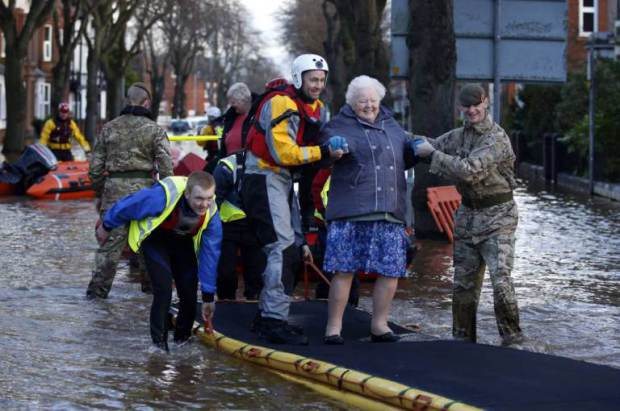 A woman is helped through flood waters by members of the RNLI and the armed forces on Warwick Street, following flooding in Carlisle. PRESS ASSOCIATION Photo. Picture date: Sunday December 6, 2015. The Environment Agency declared 130 flood warnings, while residents in some areas were evacuated from their homes. Rain continued to fall overnight in Scotland, northern England and northern parts of Wales, and is likely to continue for a few hours yet, forecasters said.See PA story WEATHER Winter. Photo credit should read: Owen Humphreys/PA Wire