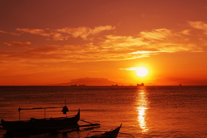 dramatic manila bay sunset with fishing boats in the foreground.